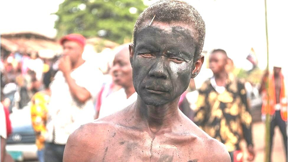 A man with a face painted with charcoal in a street of Arondizuogu during the Ikeji Festival in Nigeria