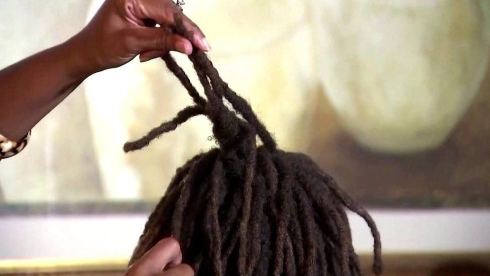 The grandmother of Amari holds up her shortened hair