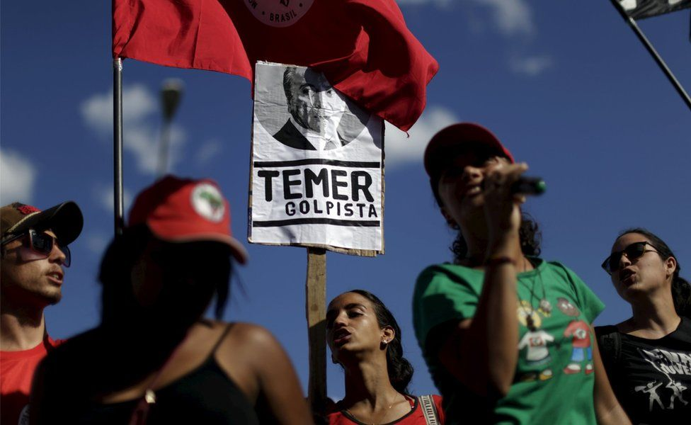"""Members of social movements hold signs during a protest against Brazil's Vice President Michel Temer in front of Jaburu Palace in Brasilia, Brazil April 23, 2016. The placard reads: """"Temer - putschist"""""""