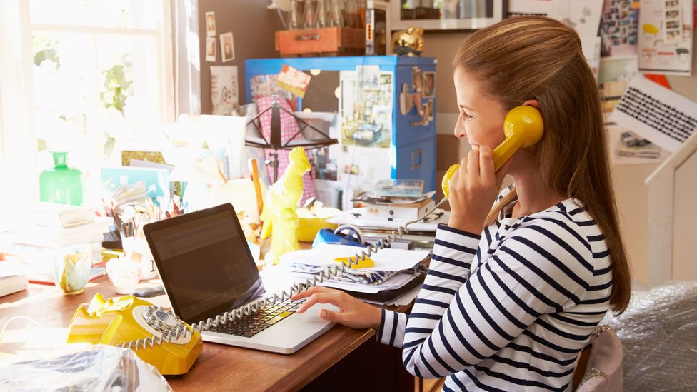A woman works at a messy desk