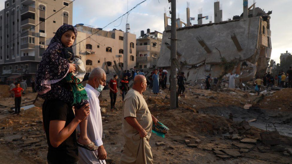 Palestinians assess the damage in Gaza after a night of air strikes by Israeli forces