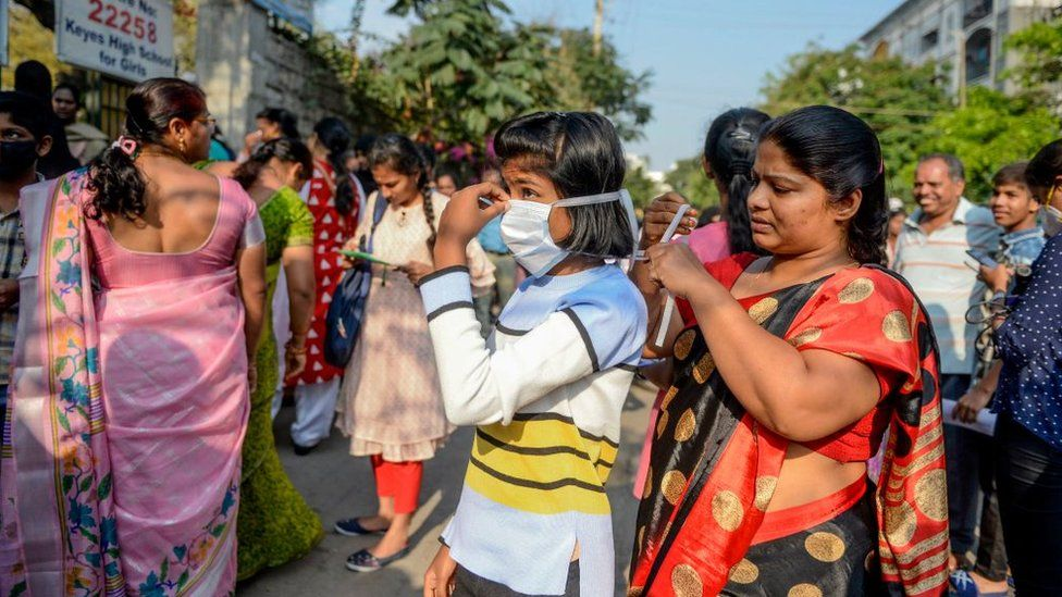 A mother ties a facemask on her daughter amid concerns over the spread of the COVID-19 coronavirus as she attends the first day of her tenth class examinations in Secunderabad, the twin city of Hyderabad, on March 19, 2020.