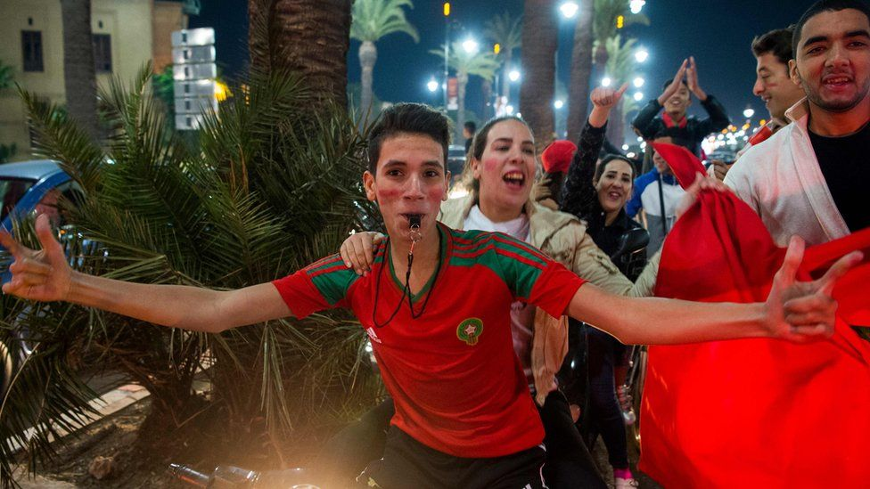 Boy wearing shirt in the Moroccan colours red and green blows a whistle as people behind him dance