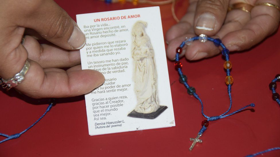 A woman holds up a prayer card and a handmade bracelet