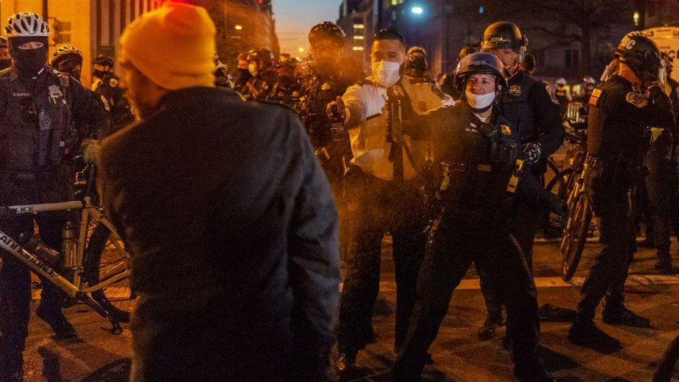 A member of the Proud Boys is pepper sprayed by the police after a confrontation with counter-protesters in Washington DC, on December 12, 2020