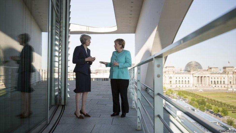 Theresa May and Angela Merkel talking at the German Chancellery