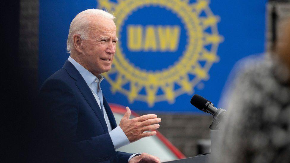 Joe Biden in front of a UAW sign