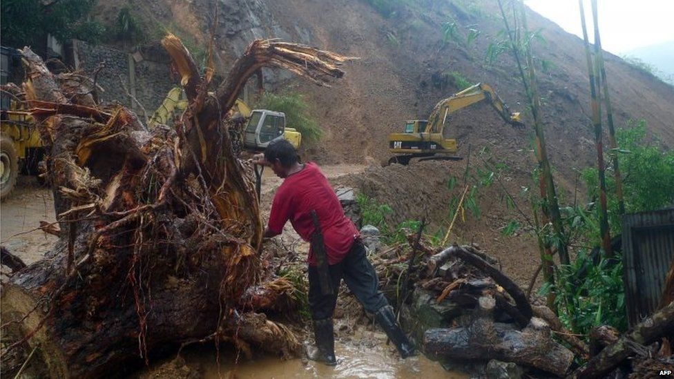 Worker cuts up fallen tree as heavy equipment clears debris and soil after a landslip due to heavy rains on a main road into Baguio City 22/08/2015
