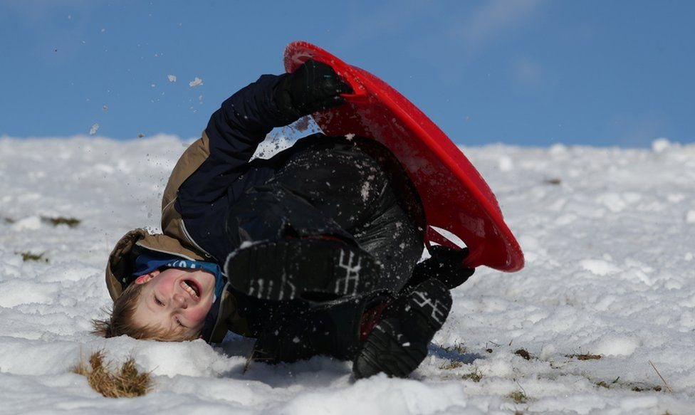 A boy sledges on a snow-covered field near Pitlochry