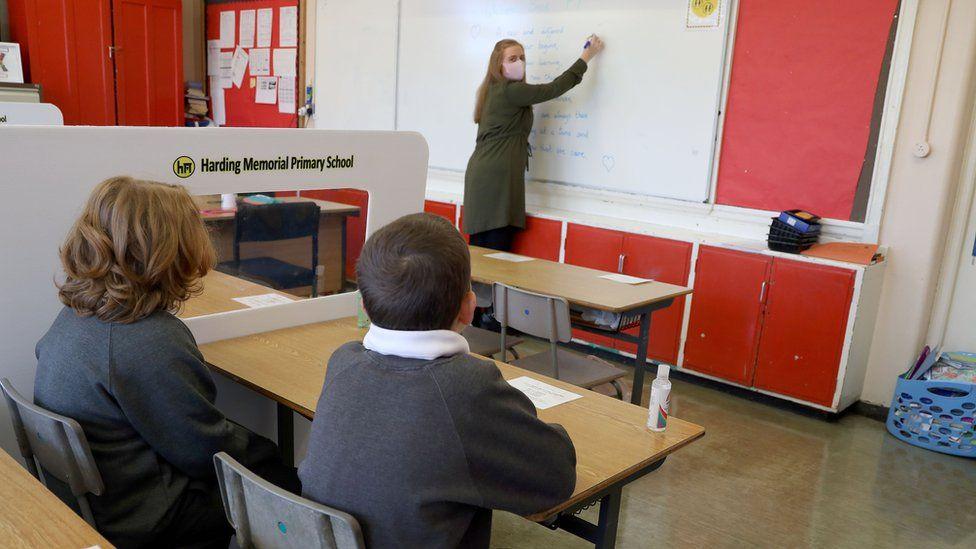 Niños sentados en un aula socialmente distante.
