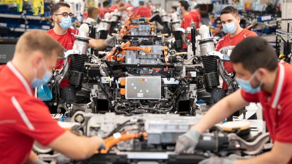 Employees of German car manufacturer Porsche wear face masks as they work on power trains for the Taycan full-electric sportscar at the production site in Stuttgart, southern Germany, on May 12, 2020,