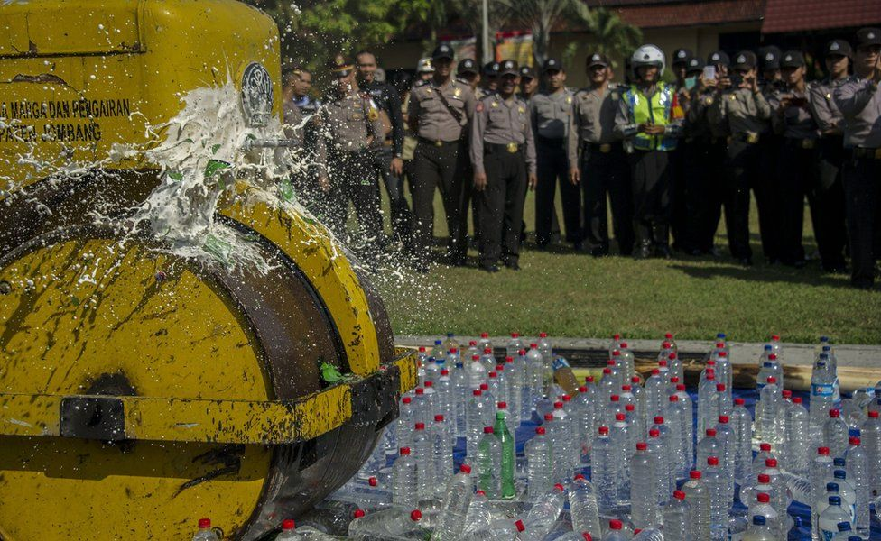 A steamroller crushes bottles of alcohol