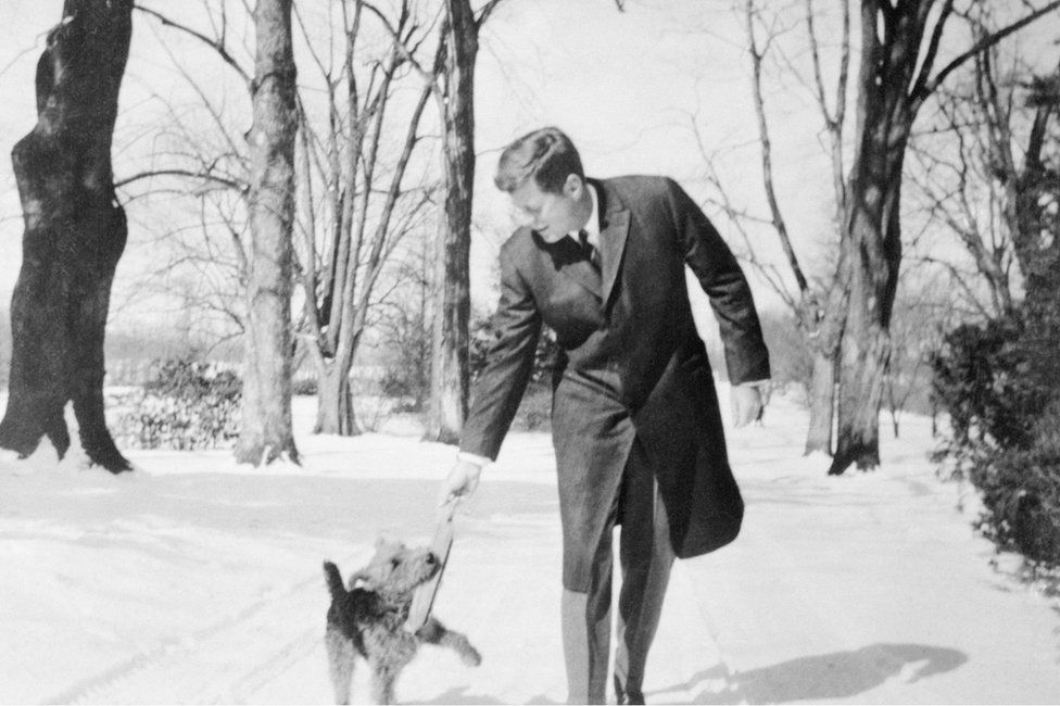 President Kennedy plays with his dog in snowy landscape