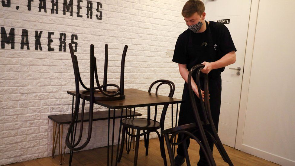 A cafe worker stacks chairs on top of a table