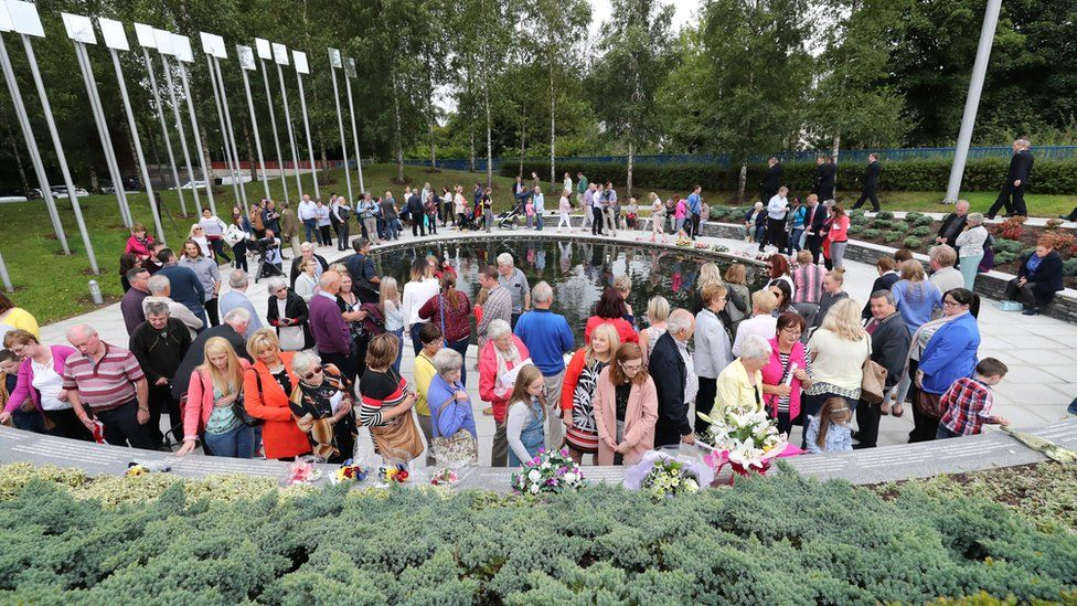 People attend a ceremony to mark the 20th anniversary of the Omagh bomb