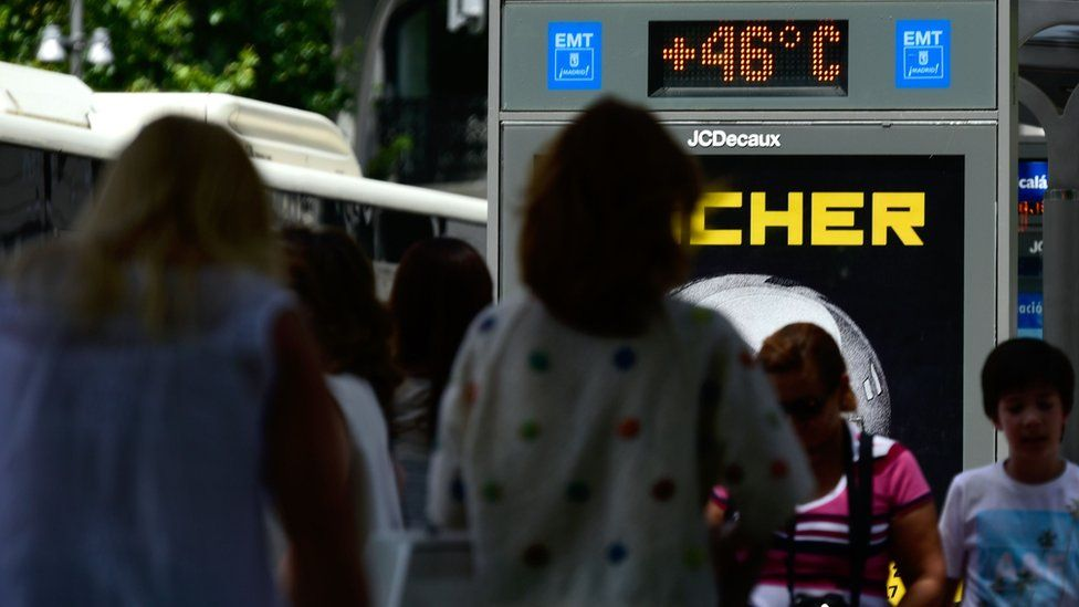 People walk past a city digital board indicating 46 degrees Celsius at a bus stop in Madrid