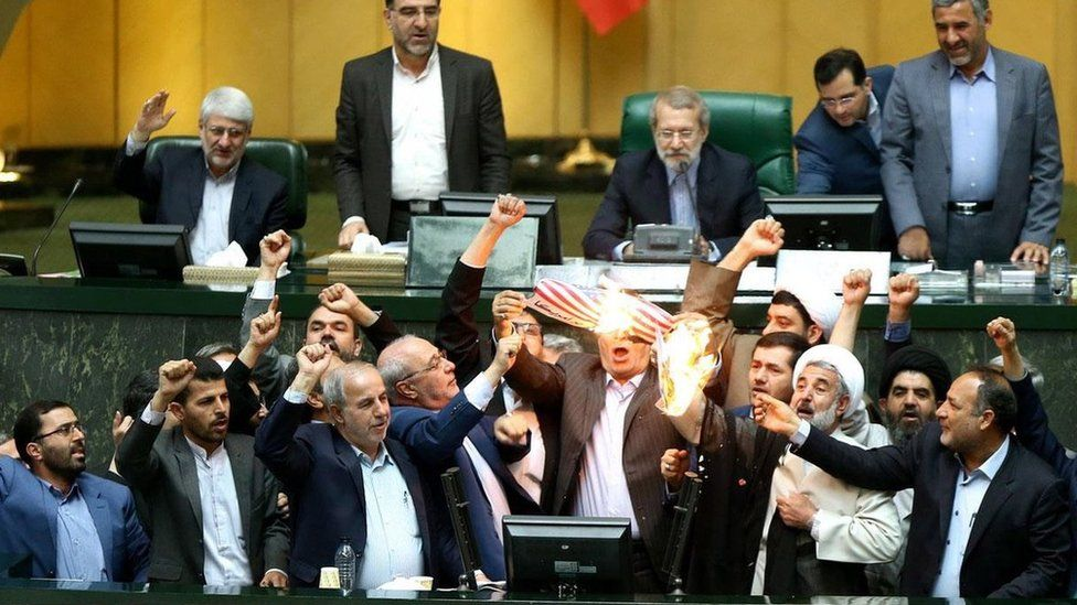Iranian MPs burn a US flag during a session at the parliament in Tehran, Iran (9 May 2018)