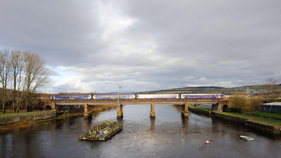A train passes over the River Leven