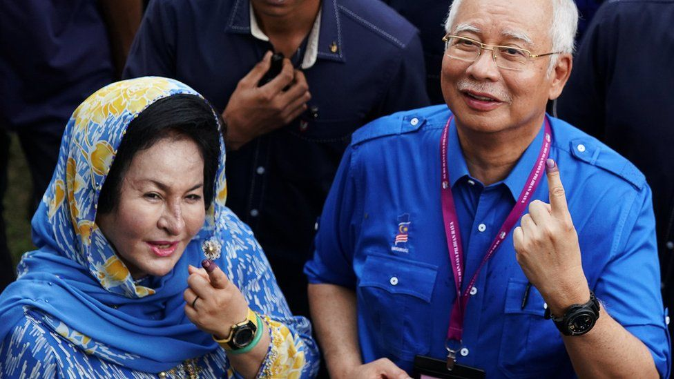 Najib Razak and his wife Rosmah show their ink-stained fingers after voting in Malaysia's general election