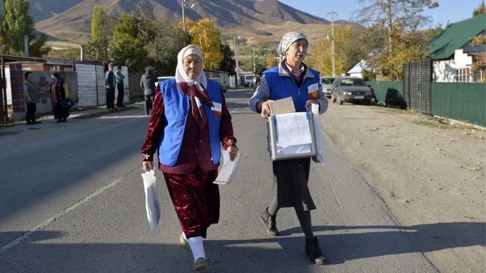 Members of a local electoral commission walk with a ballot box during an early voting in the presidential election in the village of Arashan some 20 km from Bishkek on October 14, 2017