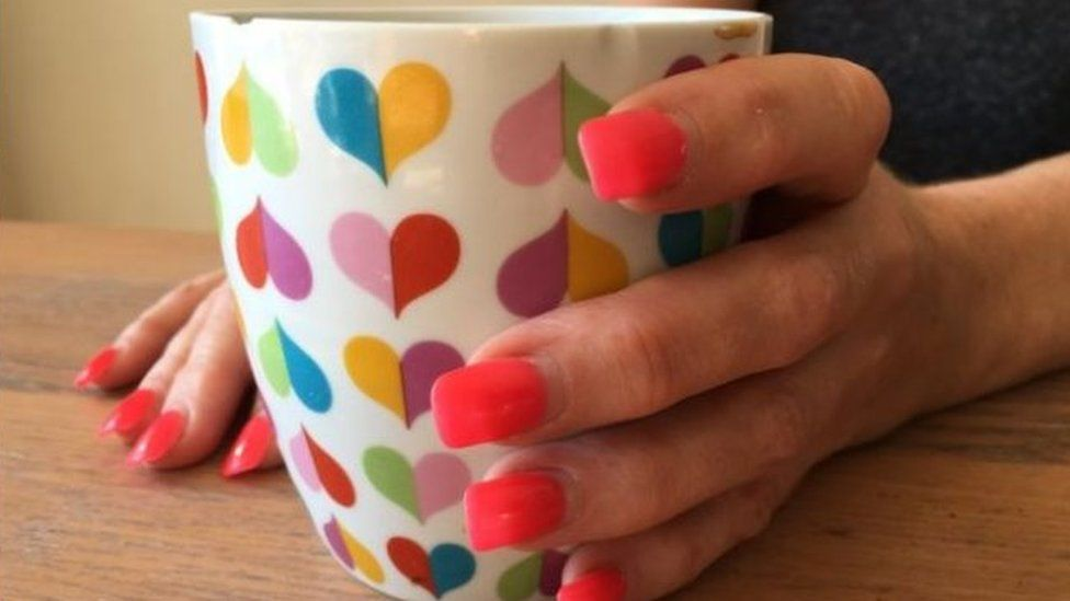 Female hand holding cup