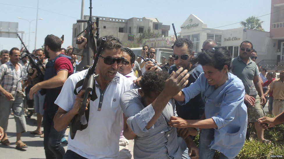 Members of the Tunisian security forces escort a man through a street in al-Sousse
