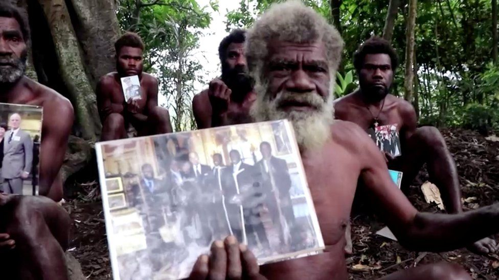 """Ikunala village Chief Yapa holds photos of himself and four other local men with Britain""""s Prince Philip, taken during their 2007 trip to England, as he sends their condolences after the prince passed away at age 99 on Friday, in Ikunala, Tanna island, Vanuatu April 11, 2021."""