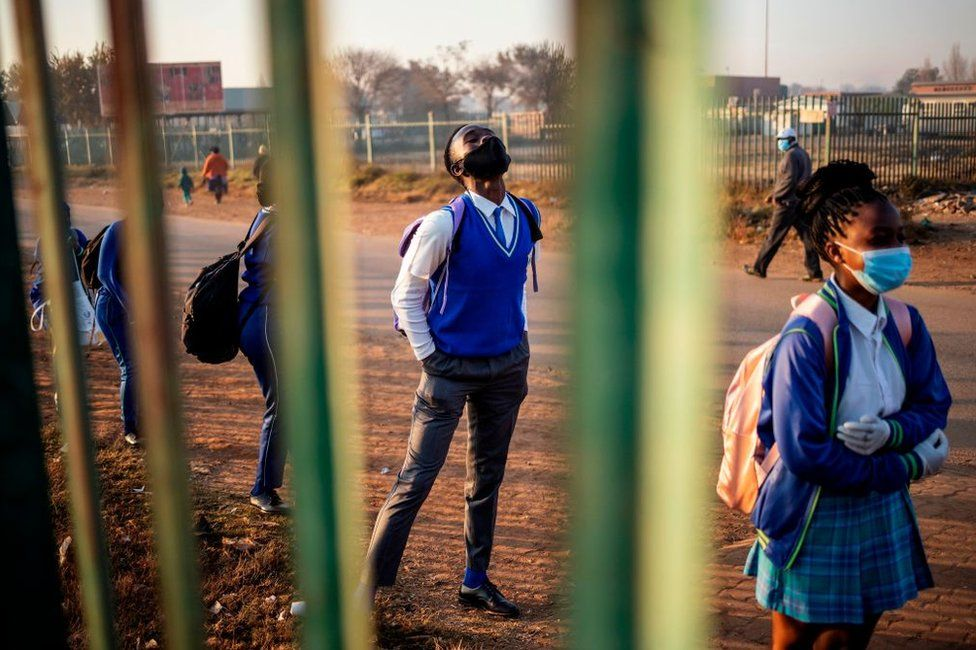 Pupils wait in line outside the school premises before classes resume in the Tembisa township, Ekurhuleni, on June 8, 2020.