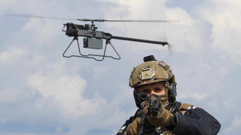 A Ghost drone hovers just behind an armed marine who is pointing his rifle at the camera