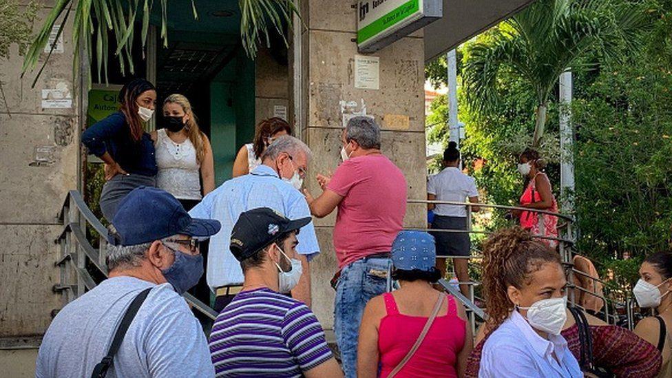 People line up outside a bank branch in Havana