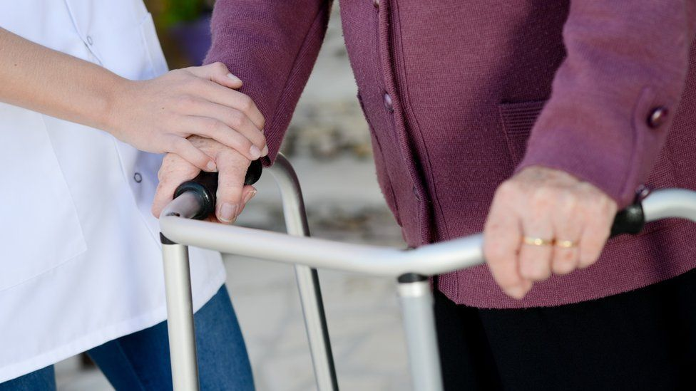 Care worker helping elderly woman