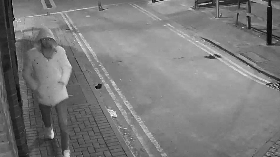 A CCTV image of a man in a light-coloured coat