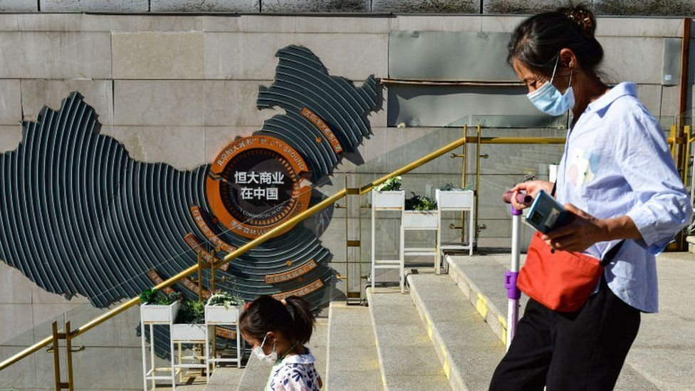 A woman with a child seen passing in front of Evergrande group's blueprint for development in China at Evergrande city square, Chaoyang District.