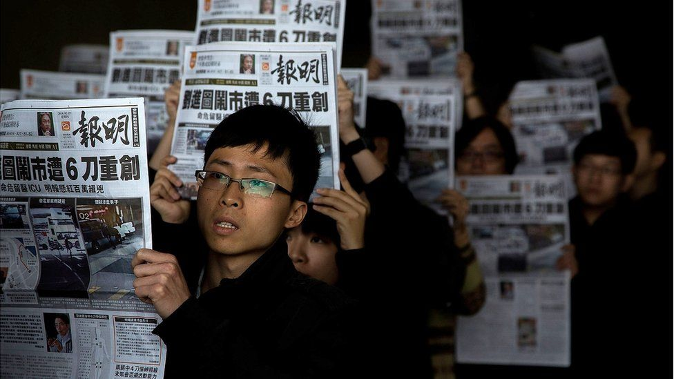Staff members of Ming Pao hold its newspaper printed on February 27, 2014 in which former chief editor of Ming Pao kevin Lau Chun-to was stabbed as front page story during protest outside the Ming Pao office, on February 27, 2014 in Hong Kong,