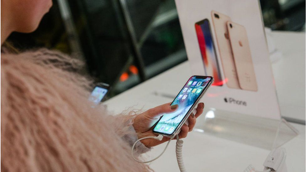 A woman tests an iPhone X