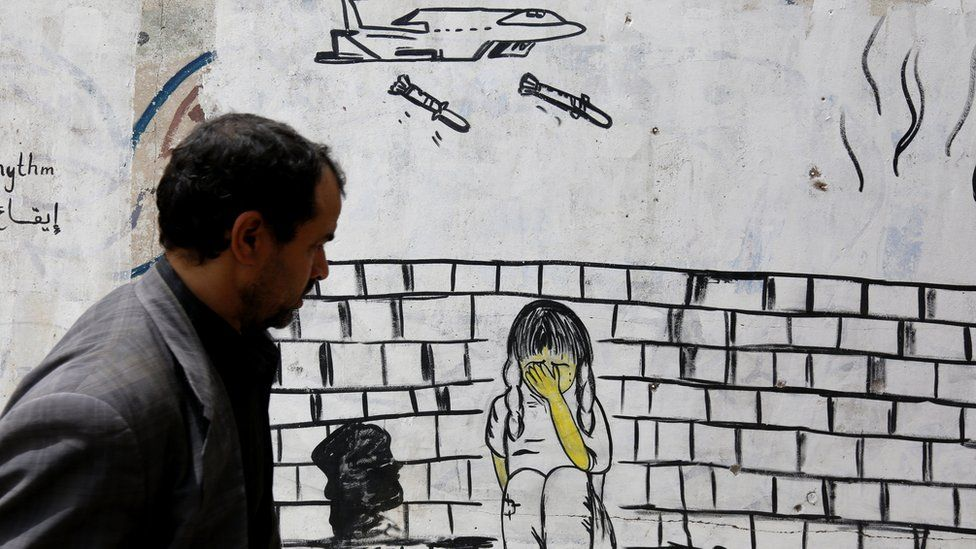 A man walks past a wall covered in graffiti depicting a warplane dropping bombs on child, in Sanaa, Yemen (10 August 2018)
