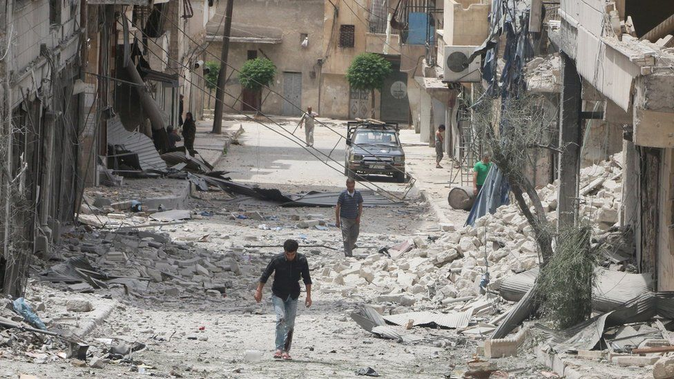 People walk past damaged buildings after an air strike in the rebel-held Baedeen district of Aleppo, Syria (3 May 2016)