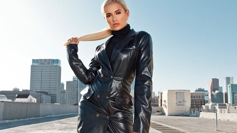 Model Molly-Mae Hague standing in a tight leather jacket and turtleneck sweater on a rooftop in Los Angeles