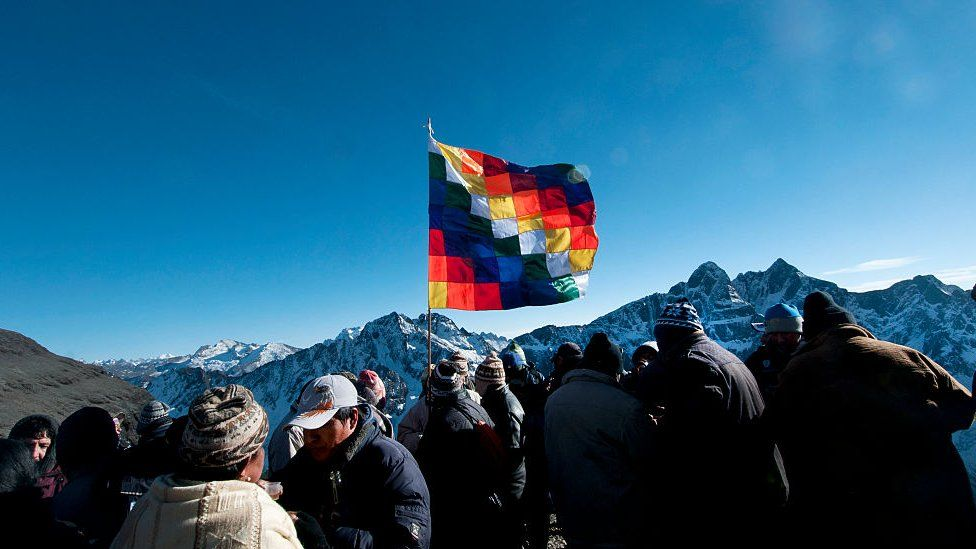 A group with the Wiphala, the co-official flag of Bolivia since 2009, with its multicoloured squares representing the native peoples of all the Andes