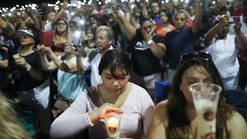 People hold up their phones in lieu of candles at an interfaith vigil for victims of a mass shooting