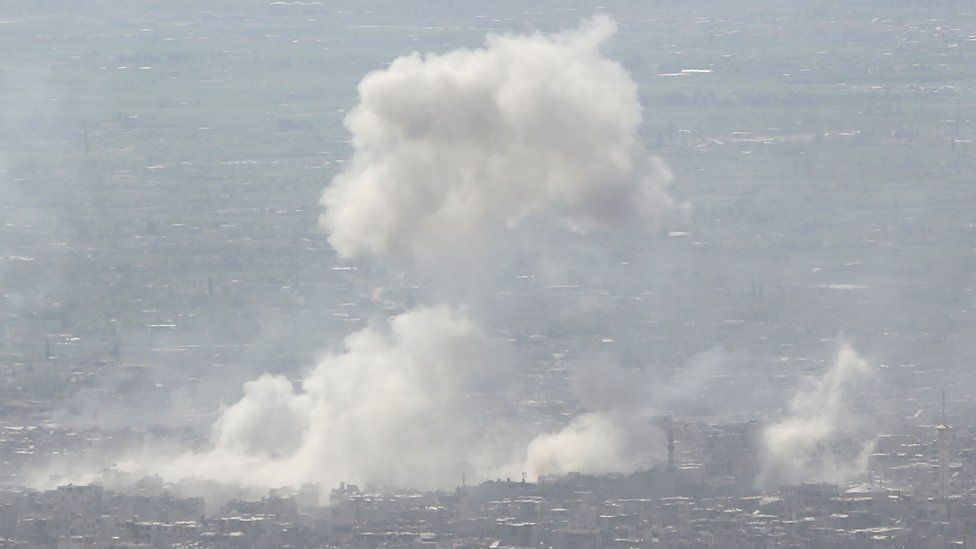 Smoke rises from Douma after a government air strike on 7 April 2018