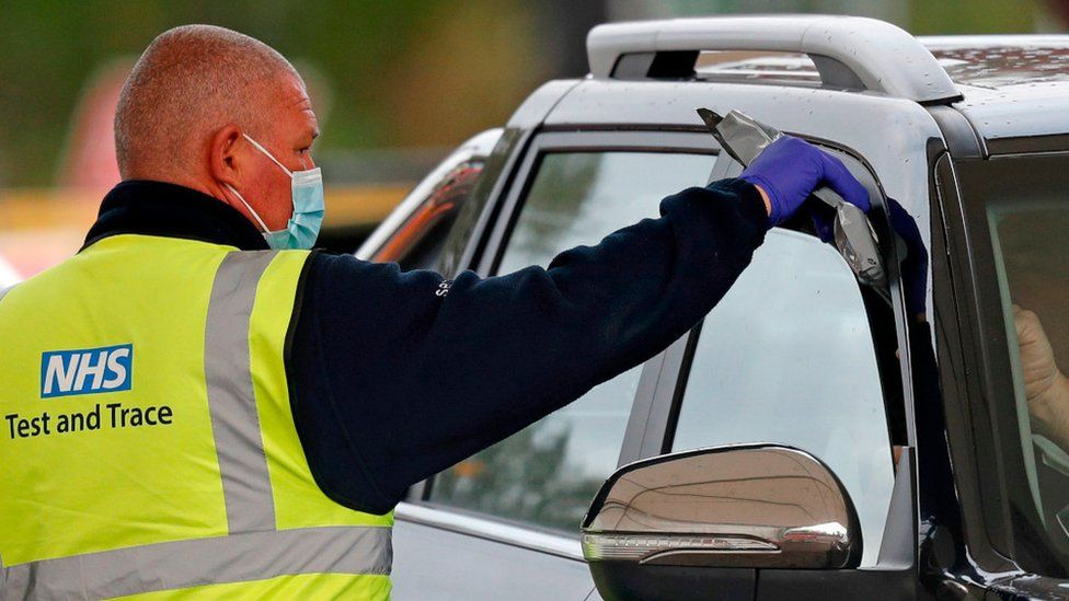 NHS employee hands test kit to person in car