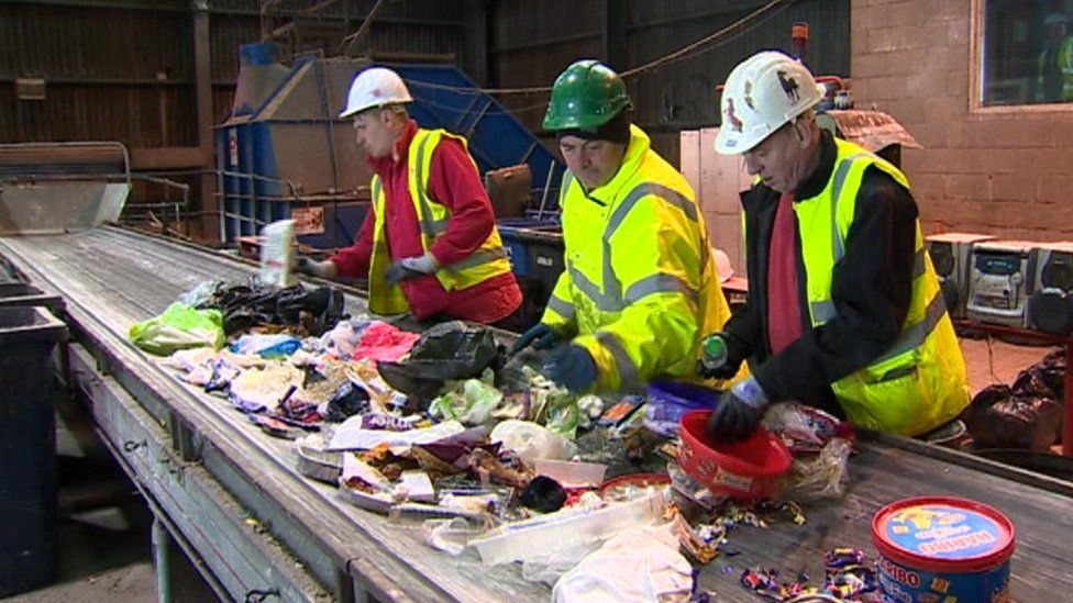 Workers sorting through recycling