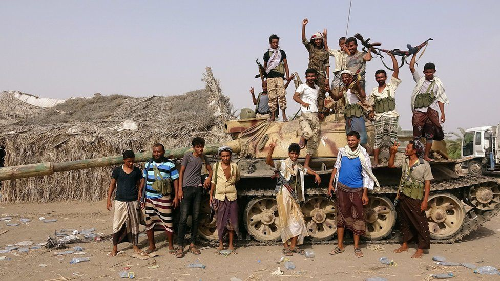 Tribal fighters allied to Yemen's government stand around a tank near Hudaydah (1 June 2018)