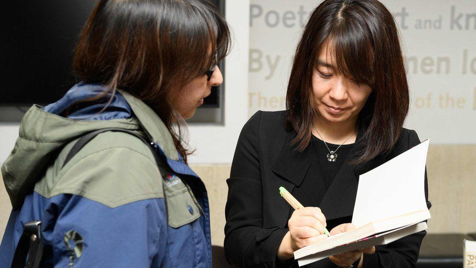 Han Kang signing a copy of her book