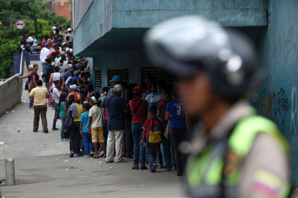 Police monitor a supermarket queue in Petare, Caracas on 1 June 2016