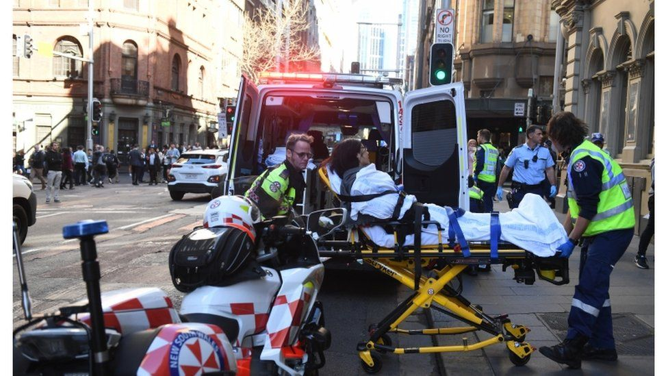 Emergency services helping a woman on a stretcher into an ambulance
