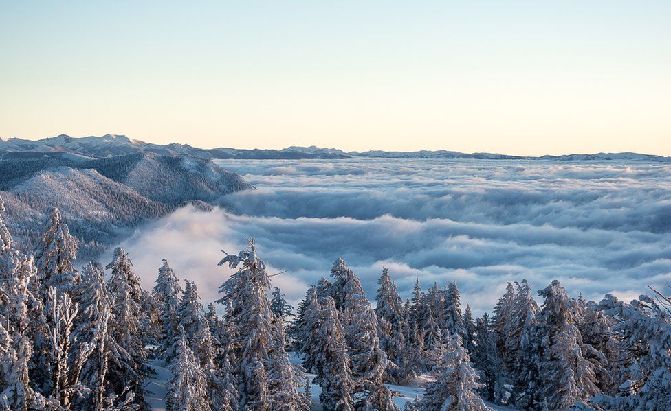 Clouds along a snowy winter landscape