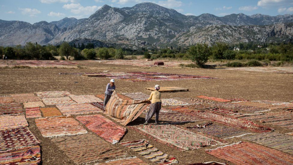 Turkish carpet-makers dry out their wares