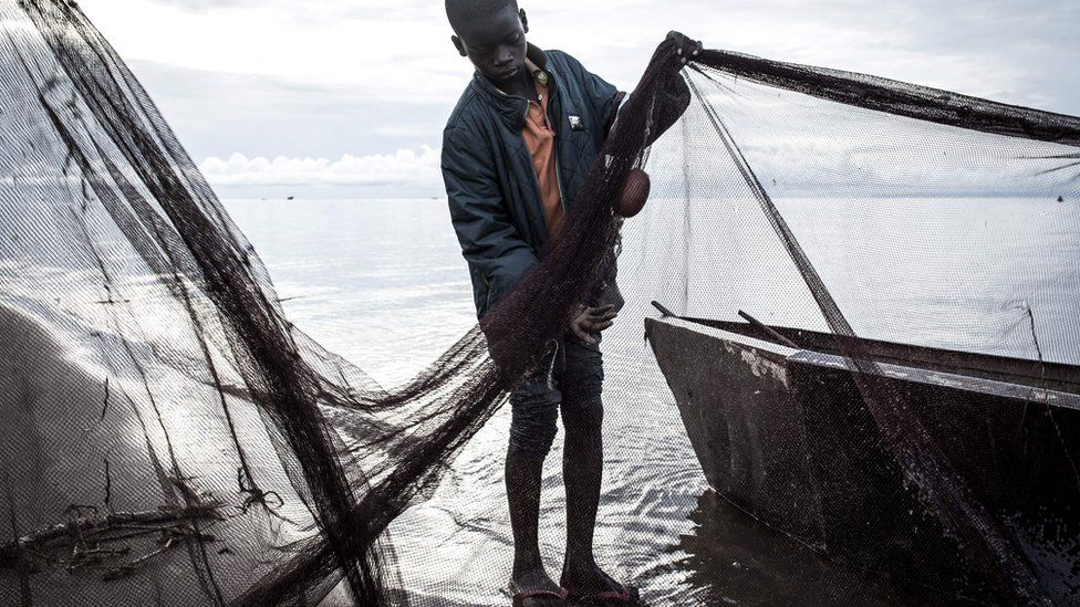 A young Congolese fisherman tends to his nets along the banks of Lake Tanganyika in Kalemie, Democratic Republic of the Congo. His trousers are rolled up and he is wearing a polo shirt with a quilted jacket over it.